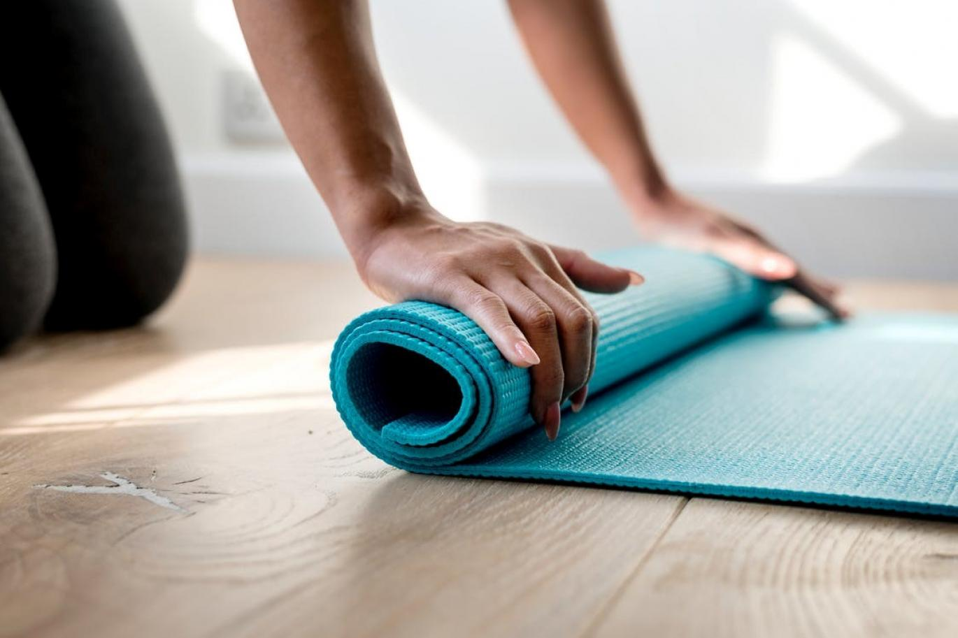 Woman rolling up a yoga mat